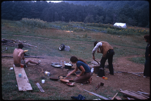 Johnson Pasture Commune: Preparing food in front of house, linking to the digital object