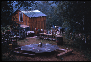 Johnson Pasture Commune: Rear view of house, laundry, and make shift table, linking to the digital object