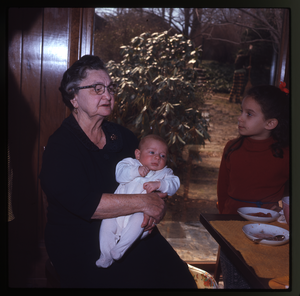 Montague Farm: Older woman holding baby (Eben) at table, linking to the digital object