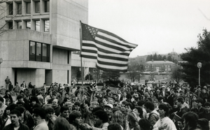 Throng of protesters on UMass campus, one waving a large American flag, linking to the digital object
