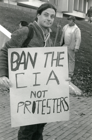 "Protester with sign reading ""Ban the CIA not protesters"" in front of Whitmore Building, UMass, linking to the digital object"