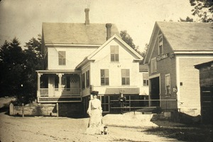 Woman and dog standing in front of feed store and stable, Wendell Depot, Mass.