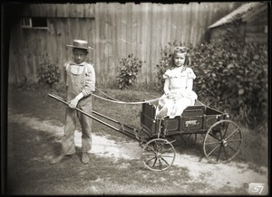 Boy pulling girl in a toy wagon (Greenwich, Mass.)