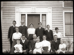 Family (?) seated by front door of a house (Greenwich, Mass.)