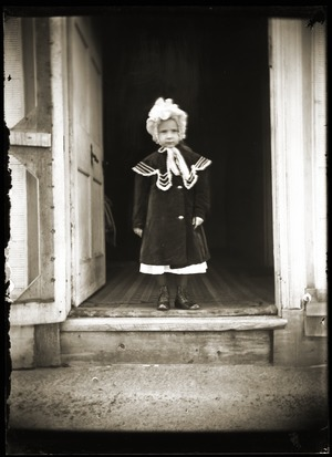 Infant girl standing in open doorway (Greenwich, Mass.)