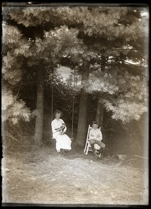 Woman, cat, and young boy seated under pine trees (Greenwich, Mass.)