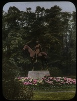 First page of Statue of woman on horseback surrounded by planting of rhododendron, trees in background