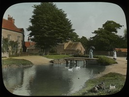 First page of Country Village, Gloucestershire, England, FAW (woman on stone footbridge over brook with ducks, village in the background)