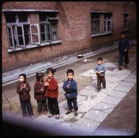 First page of Children in yard at school Young children standing in a courtyard outside their school