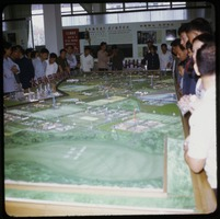 First page of Tai Ching Crowd gathered around a model for a planned city
