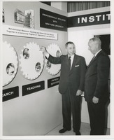 First page of Two unidentified men in front of an ICD exhibit