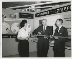 First page of Two unidentified men cutting a ribbon next to an unidentified woman holding books in front of an ICD exhibit