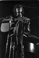 First page of Livingston Taylor in concert: Taylor on acoustic guitar (blurry image)