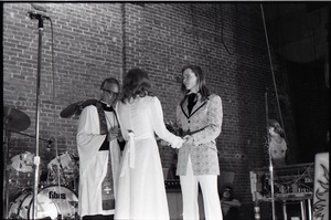 First page of Wedding of Jim and Anne Baker: exchanging vows in front of minister and drum set