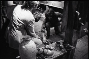 First page of Don Muller (kneeling) and unidentified man near pottery display, the Leather Shed