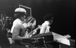 First page of Miles Davis in performance: Reggie Lucas (guitar), Cedric Lawson (keyboard), and Michael             Henderson (bass) (l. to r.)
