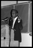 First page of James Baldwin lecturing at UMass Amherst Baldwin standing at a podium with microphones