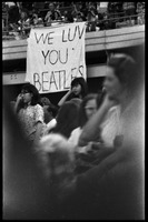 First page of Beatles concert at Shea Stadium: fans standing beneath a banner reading 'We luv             you Beatles,' hung on the overhang of the upper deck