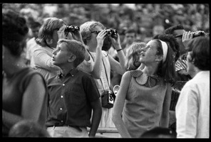 First page of Beatles concert at Shea Stadium: Beatles fans, including young boy and girl             looking up and three older fans with binoculars