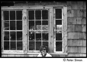 First page of Laurie Dodge standing outside a house window, Packer Corners commune