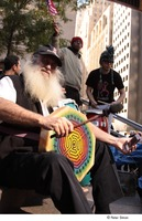 First page of Occupy Wall Street: demonstrator with a long, white beard playing a frame drum in a drum circle