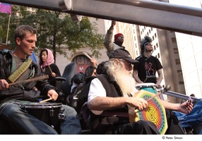 First page of Occupy Wall Street: demonstrator playing drums in a drum circle