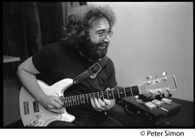 First page of Jerry Garcia: half-length portrait playing guitar