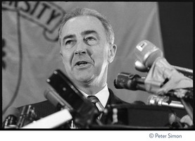 First page of Sen. Eugene McCarthy speaking at Sargeant Gymnasium, Boston University Close-up of McCarthy speaking at a podium, glancing to his right, behind a raft of microphones