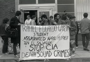 First page of Protesters in front of Student Union at UMass Amherst holding a banner reading 'Rafael Eduardo Garcia student             assassinated April 14, 1987 in El Salvador. Stop CIA death squad crimes'