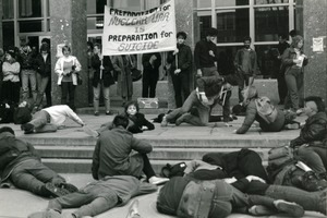 First page of Staged die-in at UMass Amherst, beneath banner reading 'Preparation for nuclear war is preparation for suicide'