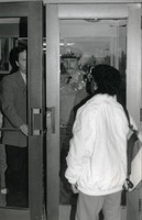 First page of Woman greeted at door of Whitmore Hall, UMass Amherst, by police officer and official
