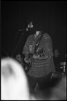 First page of Grateful Dead performing at the Music Hall: Jerry Garcia onstage, playing guitar and singing