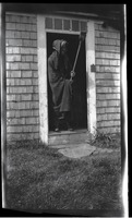 First page of Reuben Austin Snow, the cross-dressing hermit of Cape Cod, in doorway to house