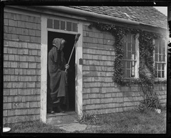 First page of Reuben Austin Snow, the cross-dressing hermit of Cape Cod, wearing a shawl,          wielding a broom, and standing in the cottage doorway