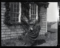 First page of Reuben Austin Snow, the cross-dressing hermit of Cape Cod, seated in front of          cottage, knitting
