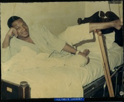 First page of Illinois Jacquet lounging on a bed in pajamas, with crutches