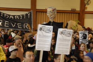First page of UMass student strike: strikers in the Student Union ballroom holding             signs supporting a general student strike, 'Solidarity forever,' and a paper machie puppet