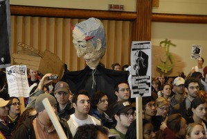 First page of UMass student strike: strikers in the Student Union ballroom holding             signs supporting a general student strike and a paper machie puppet