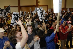 First page of UMass student strike: strikers in the Student Union ballroom holding banner,             signs, and cheering