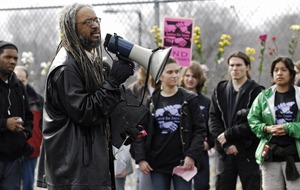 First page of Justice for Jason rally at UMass Amherst: Amilcar Shabazz, Chair of UMass             Afro-American Studies, speaks near a flower-filled fence, to students and staff who             rally in support of Jason Vassell