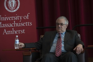 First page of Congressman Barney Frank holding a bottle of water while seated on the Student Union Ballroom stage, UMass Amherst, during his book event