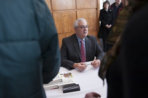 First page of Congressman Barney Frank seated at a table in the Student Union Ballroom stage,             UMass Amherst, signing copies of his biography