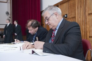 First page of Author Stuart Weisman and Congressman Barney Frank (l. to r.) seated at a table in the Student Union Ballroom stage,             UMass Amherst, signing copies of his biography