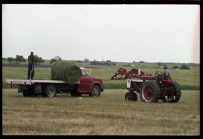 First page of Tractor loads bales of alfalfa onto a flatbed truck