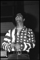First page of Abbie Hoffman in his American flag shirt, head cocked back, laughing