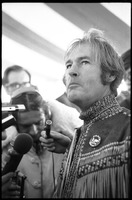 First page of Timothy Leary surrounded by press and supporters, drinking from a paper cup