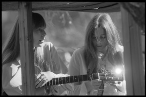 First page of Joni Mitchell with guitar, seated in her tree house in Laurel Canyon with Judy             Collins: close-up