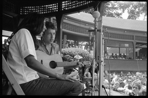 First page of Bob Dylan and Joan Baez performing on Porch #1, Newport Folk Festival View from stage right, with stands in the background