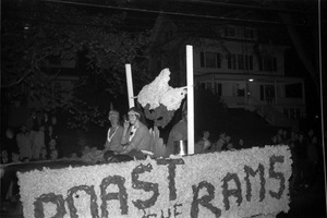 First page of Homecoming Parade (versus the University of Rhode Island) Roast the Rams -- float with 'Indian' women by goalposts