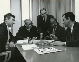First page of Five male members of business administration sitting and standing around a table